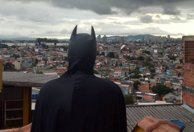 Jovem fantasiado de Batman olhando para o horizonte de casas do Capão Redondo.