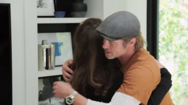 Brad Pitt embraces his friend, Jean, in Black, during the program