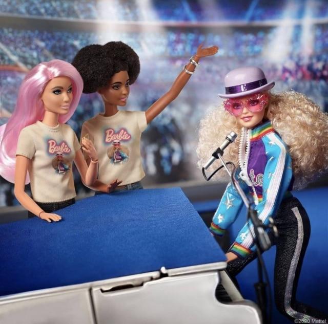 Barbie com look inspirado em Elton John, enquanto toca piano em uma das icônicas apresentações do cantor