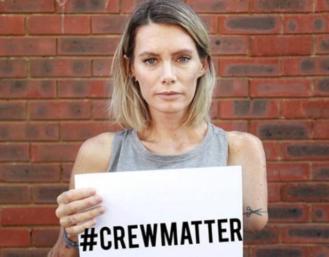 A dublê Olivia Jackson com uma placa que diz 'A Equipe Importa', alertando para acidentes com envolvidos em gravações de filmes