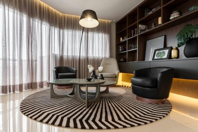 Tapete redondo demarca área de estar em apartamento decorado por Ale Rovito