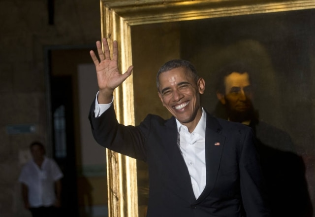 President Barack Obama waves to journalists next to a painting of President Abraham Lincoln at Havana's City Museum during a visit to Old Havana, Cuba, Sunday, March 20, 2016. Obama's trip is a crowning moment in his and Cuban President Raul Castro's ambitious effort to restore normal relations between their countries. (AP Photo/Ramon Espinosa)