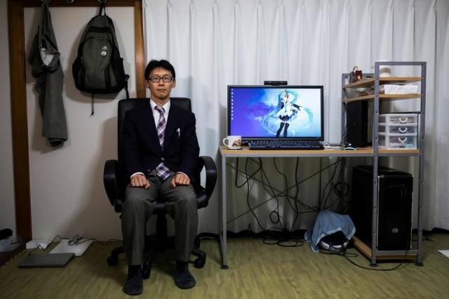 Akihiko Kondo posa em sua casa com a figura virtual com quem se 'casou'.