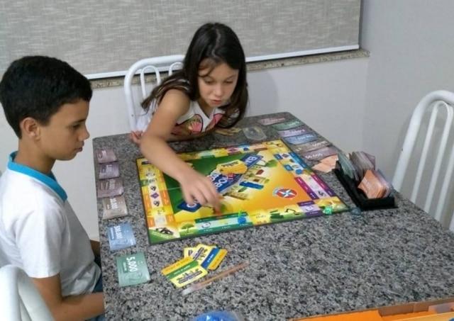 Pedro, de 12 anos, e Manuela, de 8, brincam com jogo de tabuleiro durante as férias.