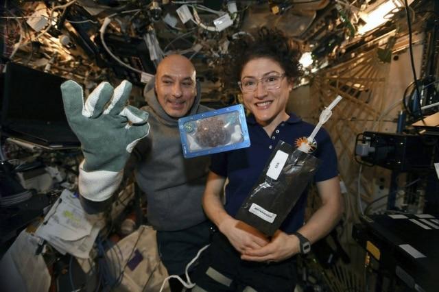 A astronauta Christina Koch e o astronauta italiano Luca Parmitano com um dos cookies assados na Estação Espacial Internacional.