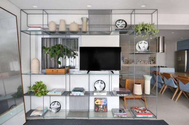 A estante de metal como suporte para a televisão e as obras de arte