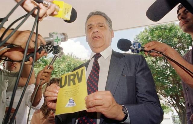 O ministro da Fazenda Fernando Henrique Cardoso segura a cartilha da URV (Unidade Real de Valor) enquanto concede entrevista na porta do Ministério, em Brasília, DF. 01/3/1994. Foto:Wilson Pedrosa/Estadão
