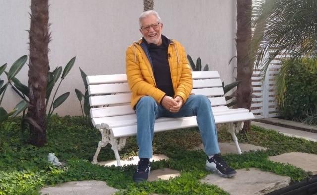 Carlos Alberto de Nóbrega sentado nobanco de 'A Praça É Nossa' que guarda em sua casa