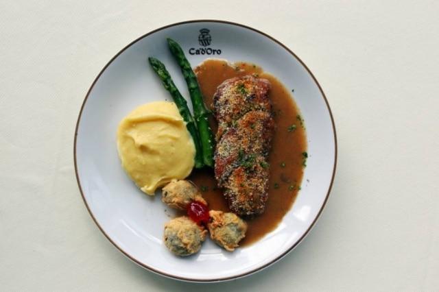 Peito de pato à Colleoni. Clássico da casa, o peito da ave é envolto em crosta crocante de ervas e chega à mesa no prato acompanhado de aspargos, purê de batata e três figos empanados
