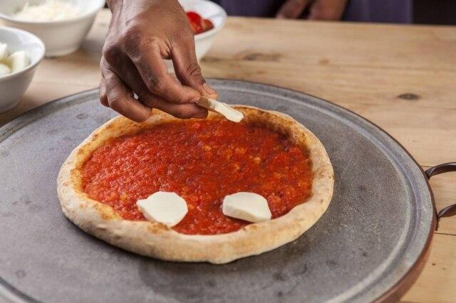 Não faça camadas, distribua bem os ingredientes da cobertura da pizza.
