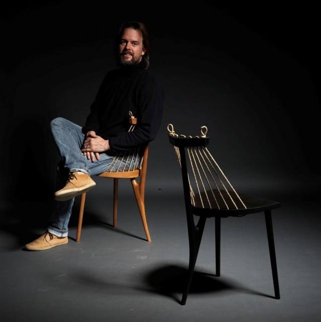 O ebanista Ricardo Graham Ferreira com um de seus best-sellers, a cadeira 3 pés
