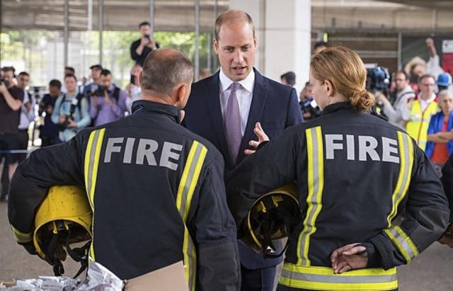 Príncipe William com bombeiros durante visita ao abrigo temporário destinado aos moradores que ficaram sem teto após o incêndio na Grenfell Tower.