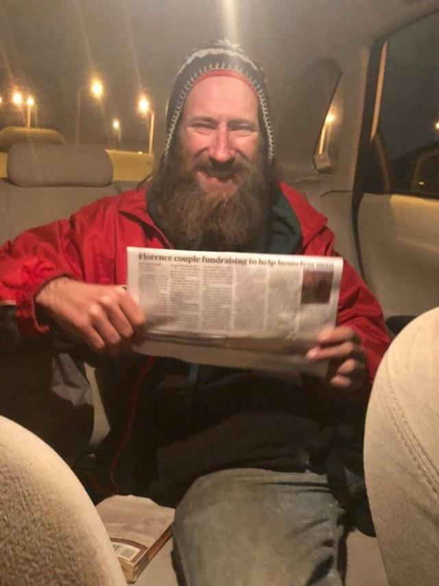 Johnny Bobbit Junior segurando um jornal que noticiou a campanha.