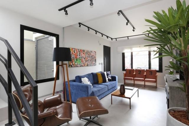 Mesa de centro de Fernando Jaeger e poltrona Charles Eames compõem a decoração da sala de estar, logo na entrada do sobrado