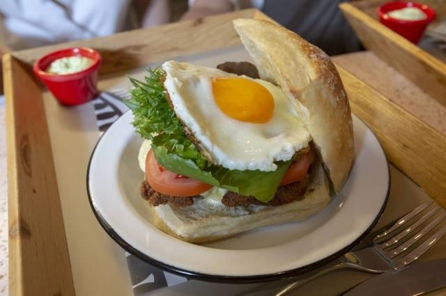Chivito, clássico sanduíche uruguaio, com bife àmilanesa,ovo frito e, aqui, pão de fermentação natural.