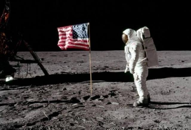 Astronauta Buzz Aldrin ao lado de bandeira dos EUA fincada na Lua.