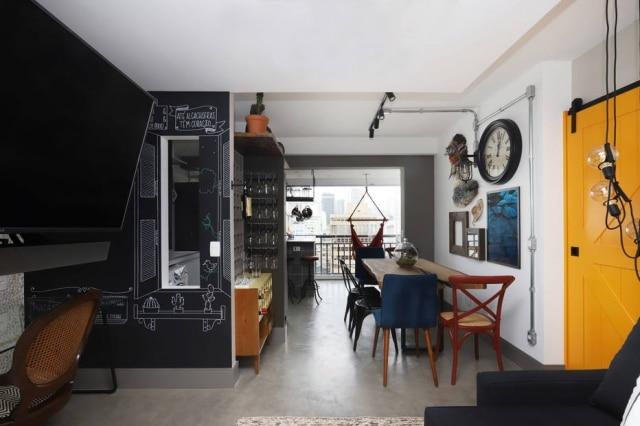 A vista do 14º andar pode ser apreciada da sala de estar, graças à integração da varanda. A parede do home office na sala tem frases desenhadas, criadas pelo casal