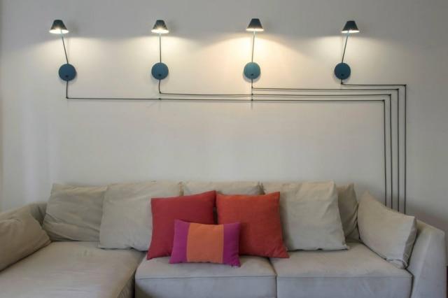 Detalhe da instalação na sala de TV com arandelas alinhadas feita pelo Casa2 Arquitetos