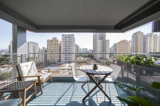 Varanda coberta com piso azul é o grande destaque do apartamento