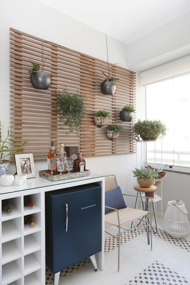 Treliça de madeira funciona como solução para acomodar plantas e imprimir a atmosfera rústica típica das casinhas de praia.