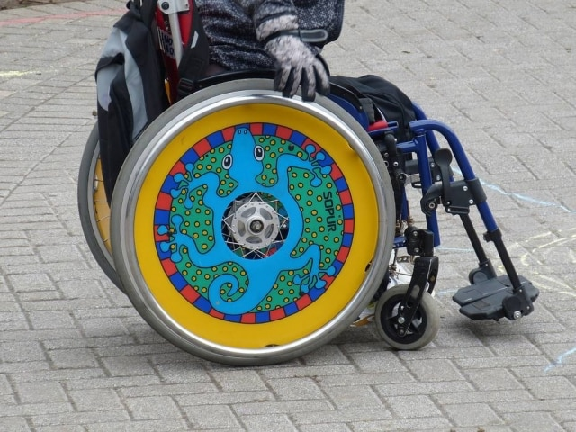 Conforme a doença progride, usar cadeira de rodas torna-se necessário.