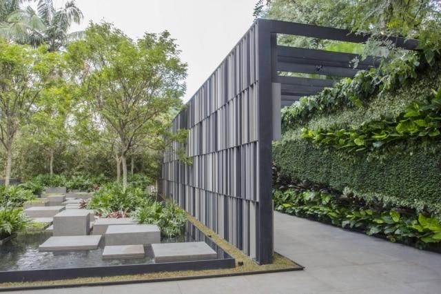 O pergolado de entrada com denso jardim vertical e parede com brises desenhados por Alex Hanazaki