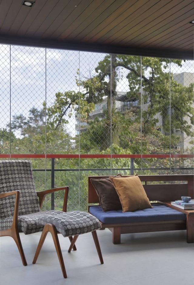 Varanda do apartamento dá de cara para copas de árvores, trazendo clima de frescor ao local