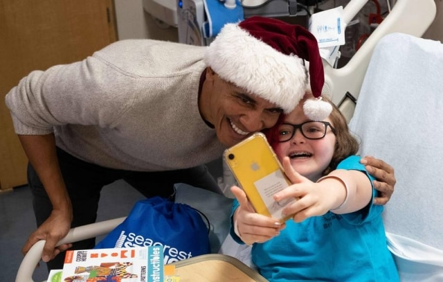 Barack Obama tira selfie ao lado de paciente em hospital infantil de Washington.