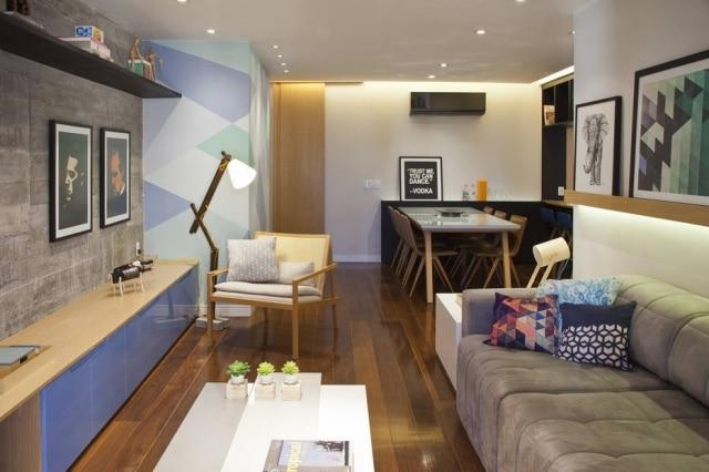 Estilo urbano realçado pelo concreto da parede e objetos de decoração na sala de estar