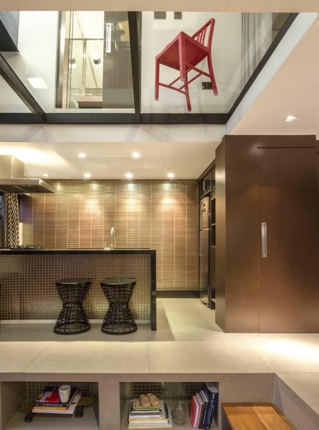 Vista da cozinha a partir do ambiente de estar, tendo acima o segundo pavimento do duplex