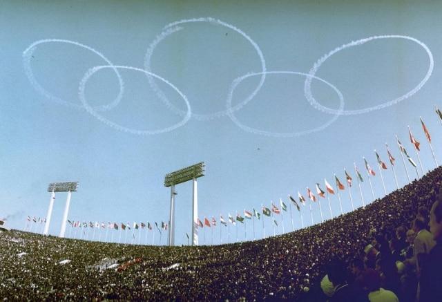 Jatos da Força Aérea do Japão desenham o símbolo olímpico no céu durante a cerimônia de abertura dos Jogos de 1964.