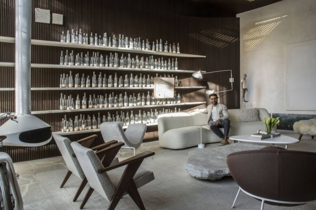 Nildo José posa em seu ambiente. Acima, sombra de claraboia realça estante preenchida com garrafas de areia
