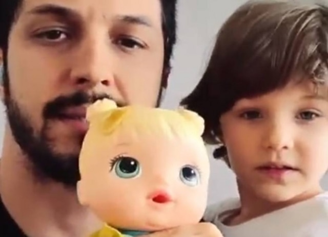 Romulo Estrela mostra a boneca de seu filho, Theo
