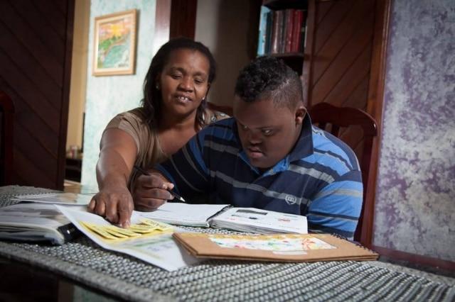 Trissomia do cromossomo 21afeta brancos e negros da mesma forma, mas só uma em cem fotos no Google sobre o tema mostra afrodescendentes. Na imagem, Evanira conversa com seu filho, o Alexsander.