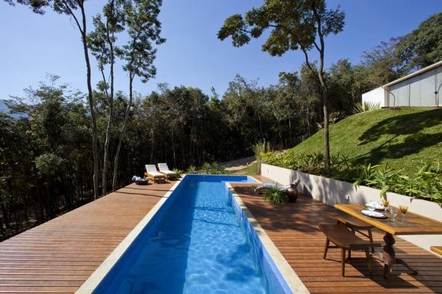 A piscina fica na entrada do terreno neste projeto de Estela Netto nos arredores deBelo Horizonte