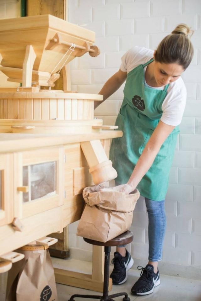 Alethea Suedt, d'A Padeira, e seu moinho horizontal que permite escolher diferentes refinamentos da farinha de trigo, da integral à branca