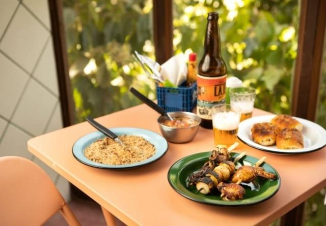 Churrasco na laje do bar Pirajá tem espetinhos, cerveja em garrafa, vinagrete e farofa