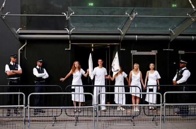 Policiais fazem a segurança na entrada principal da Semana de Moda de Londres enquanto ativistas bloqueiam a passagem.
