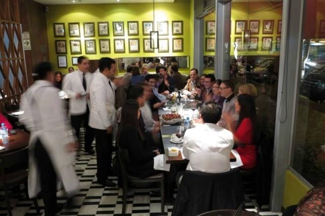 Clientes em restaurante rodeados por garçons, que agora têm curso de formação superior em São Paulo