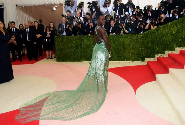 A atriz Lupita Nyong'o usou Calvin Klein verde metalizado e complementou o visual com coque alto