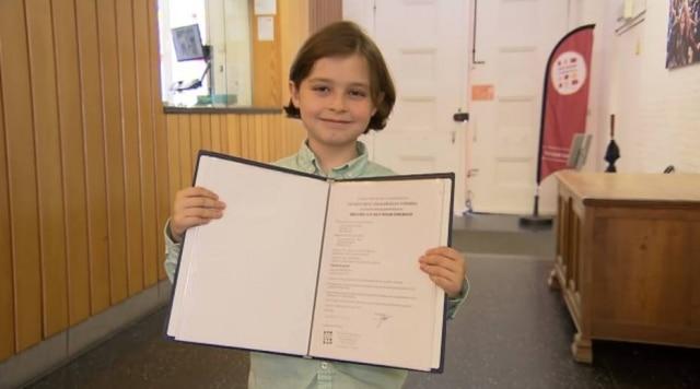 Laurent Simons mostra seu certificado de conclusão do ensino médio.