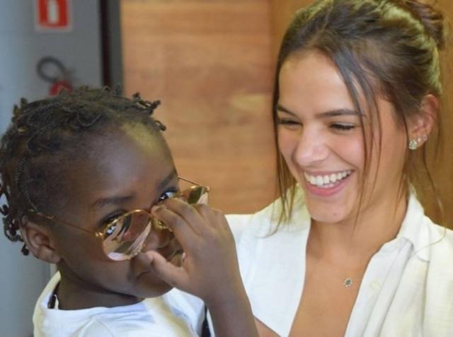 Bruna Marquezine e uma criança refugiada durante evento em São Paulo.