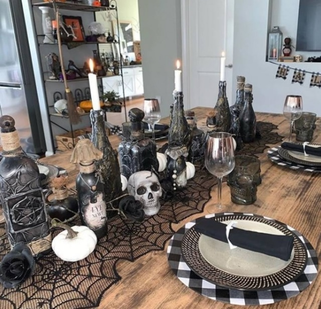 Teias de aranha servem como arranjo de mesa central que sustentam velas, caveiras e garrafas que imitam poções