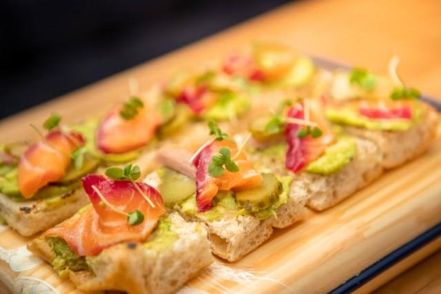 Pão da Padaria da Esquina comlaranja esemente de coentro na receitaé base para as tartines, entre elas a coberta com avocado, picles de pepino e gravlax de salmão com beterraba.