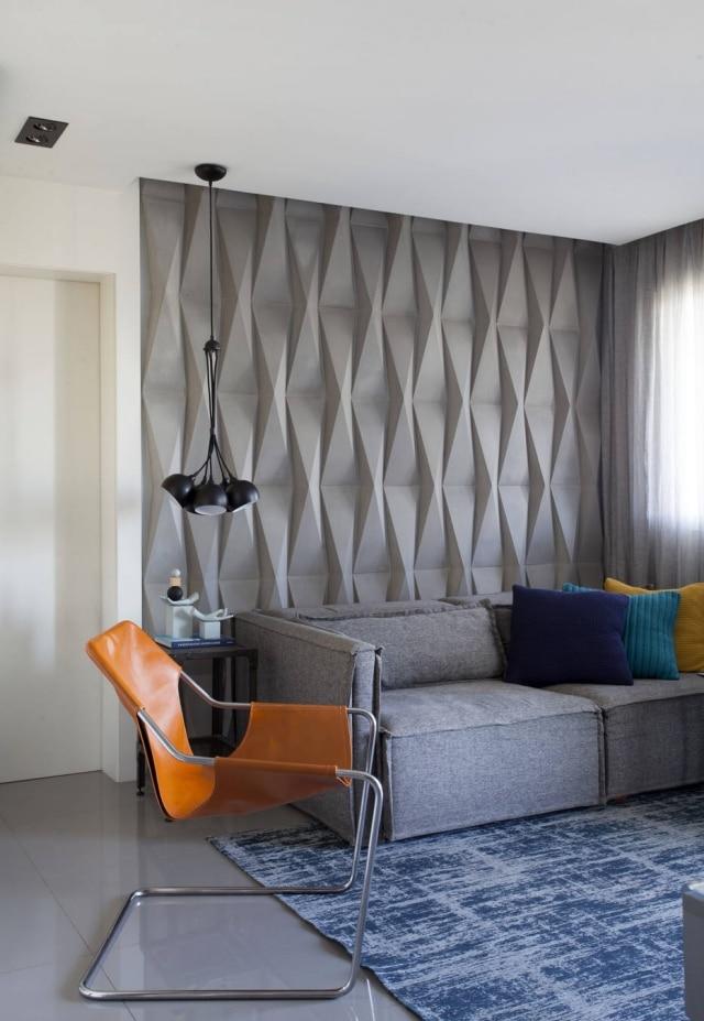 Revestimento comentício decora parede de sala em projeto de Ricardo Abreu