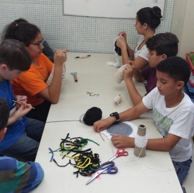 Meninos e meninas envolvidos da confecção de peças de crochê que são levadas por eles para casa.