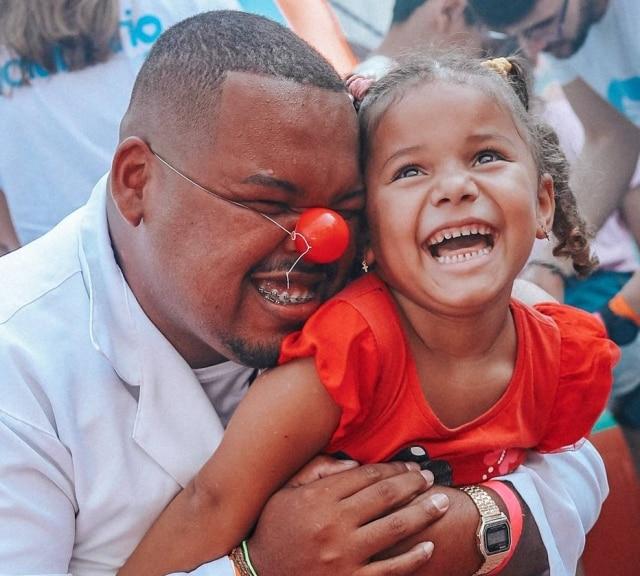 Voluntário da Hamburgada do Bem interage com criança durante evento do projeto.